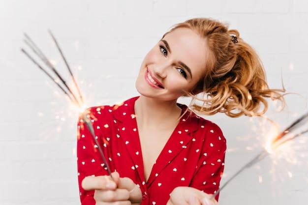 Senhora de olhos azuis rindo enquanto acenava as luzes de bengala. modelo feminino caucasiano de cabelos loiros de close-up segurando estrelinhas na manhã de ano novo.