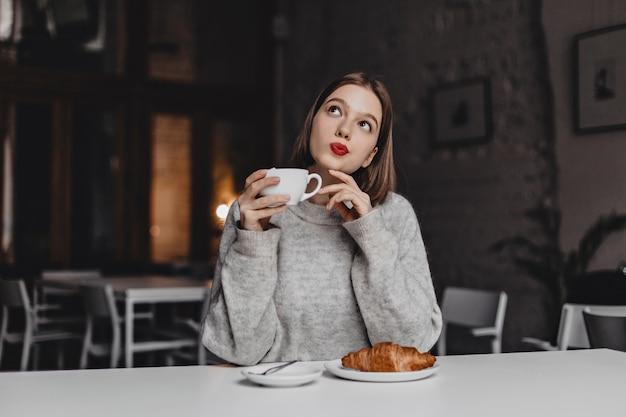 Senhora de olhos castanhos com batom vermelho, posando pensativamente com uma xícara de chá. mulher de suéter cinza sentado à mesa com croissant.