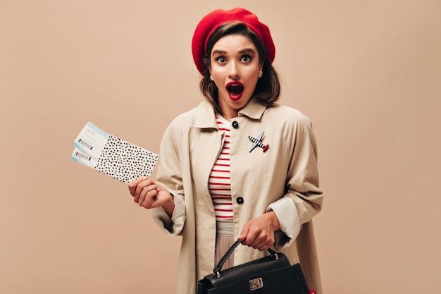 Senhora de olhos castanhos na boina vermelha parece surpresa e tem ingressos. menina parisiense elegante em elegante casaco de outono e chapéu brilhante olha para a câmera.