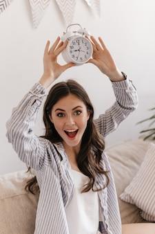 Senhora de olhos verdes de pijama posando feliz em um apartamento e segurando um despertador