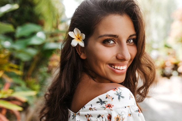 Senhora de olhos verdes e pele bronzeada sorrindo docemente contra a parede de palmeiras