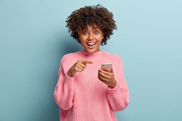 Senhora de pele escura, positiva e surpresa aponta para dispositivo de telefone inteligente, sugere ter uma conversa no bate-papo em grupo, feliz por receber muitas mensagens de parabéns na caixa de correio, tem olhar radiante