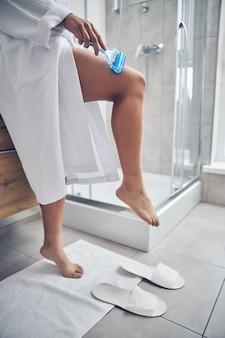 Senhora de roupão fazendo massagem de drenagem linfática em um banheiro