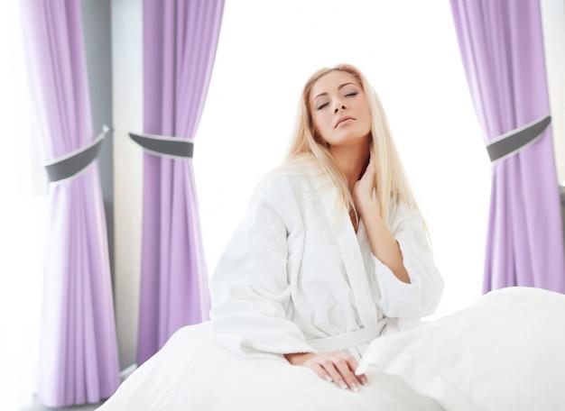 Senhora de roupão, sentada na cama.