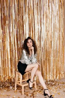 Senhora de saia preta e top prata sentada sobre fundo dourado