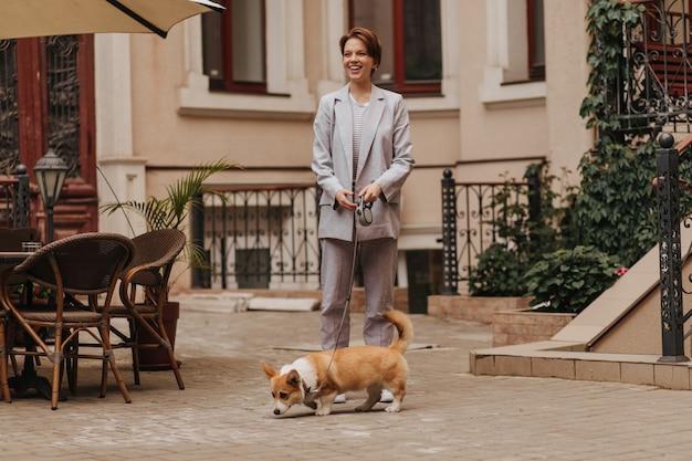 Senhora de terno cinza caminha com seu corgi. retrato de mulher feliz em jaqueta e calça posando com cachorro do lado de fora