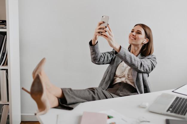 Senhora de terno cinza e sapatos de salto bege leva selfie no local de trabalho contra uma parede branca.