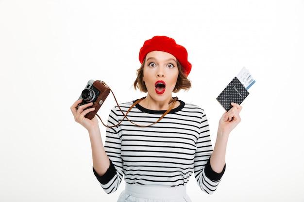 Senhora de turista surpresa com câmera segurando o passaporte com bilhetes.
