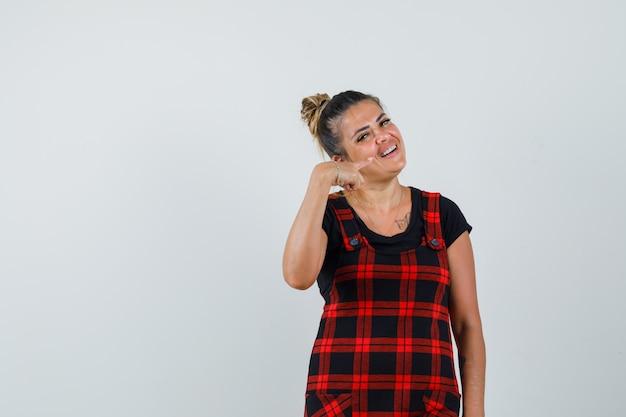 Senhora de vestido avental apontando para os dentes e parecendo alegre, vista frontal.