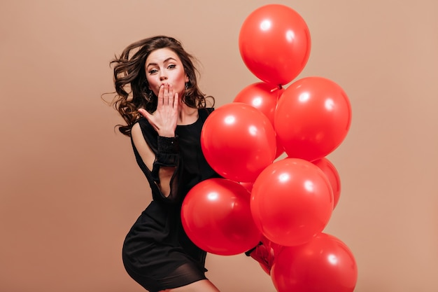 Senhora de vestido preto curto poses em fundo bege com beijo de balões e sopros.