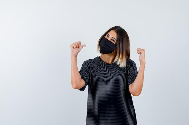 Senhora de vestido preto, máscara médica apontando para trás com os polegares e olhando alegre, vista frontal.