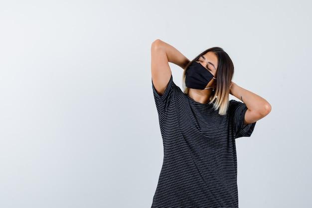 Senhora de vestido preto, máscara médica, segurando as mãos atrás da cabeça e parecendo relaxado, vista frontal.