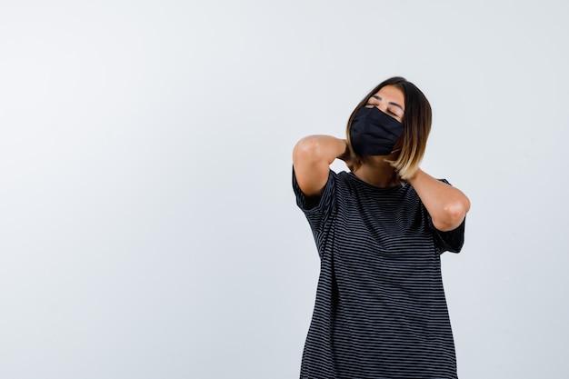 Senhora de vestido preto, máscara médica, segurando as mãos no pescoço e olhando em paz, vista frontal.