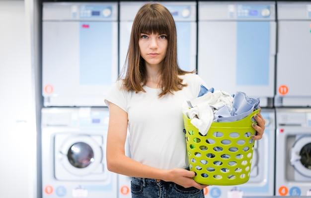 Senhora de vista frontal, segurando o cesto de roupa suja