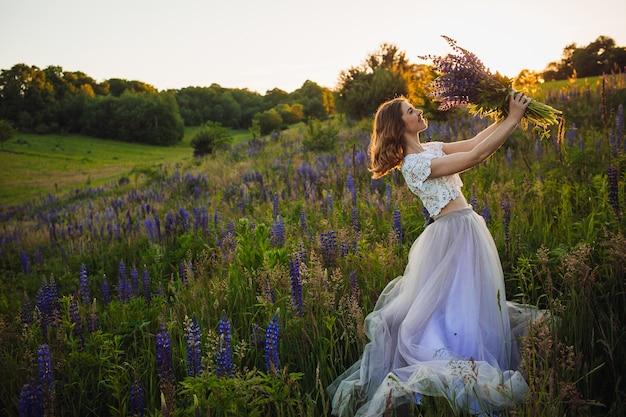Senhora deslumbrante com vestido branco fica com buquê no campo