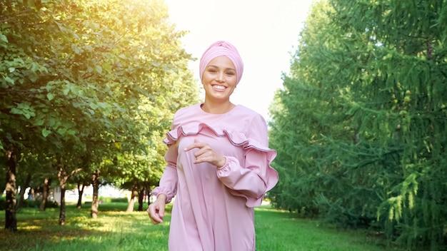 Senhora desportiva com vestido roxo com hijab corre ao longo do caminho do parque verde e sorri alegremente sob o sol forte num dia de verão