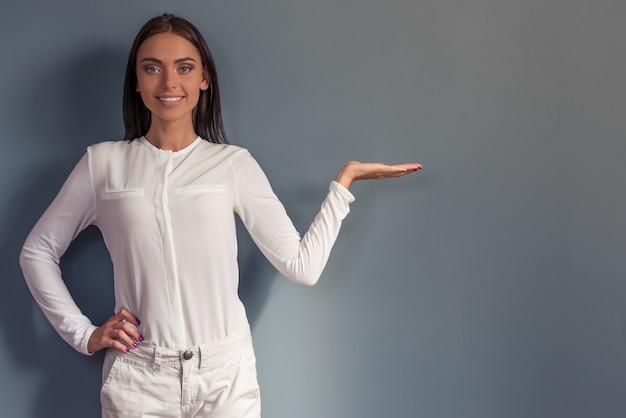 Senhora do negócio atraente na roupa está apontando para o lado.