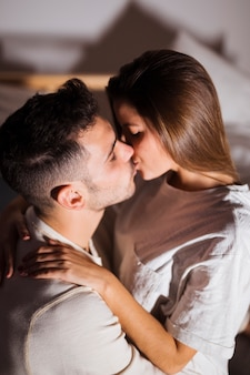 Senhora e cara beijando e abraçando na cama no quarto escuro