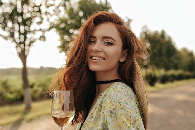 Senhora elegante com cabelo ondulado ruivo e bandagem preta no pescoço, em um vestido verde moderno, sorrindo e segurando um copo com bebida ao ar livre
