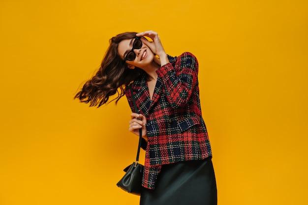 Senhora elegante com jaqueta listrada vermelha e óculos posando na parede amarela