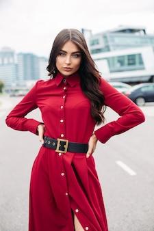 Senhora elegante confiante num vestido vermelho, posando para a câmera, segurando as mãos na cintura. moda feminina