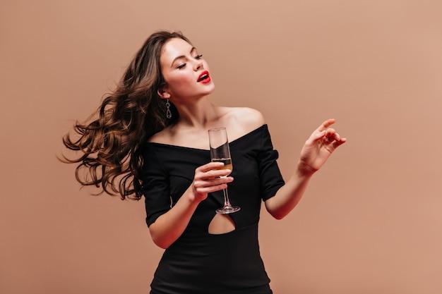 Senhora elegante de vestido preto, segurando uma taça de vinho espumante no fundo bege.