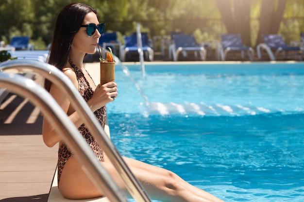 Senhora elegante descansando no resort, sentado perto da piscina com as pernas na água de férias