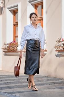 Senhora elegante em saia de couro e camisa branca andando pela rua com bolsa de mão de couro