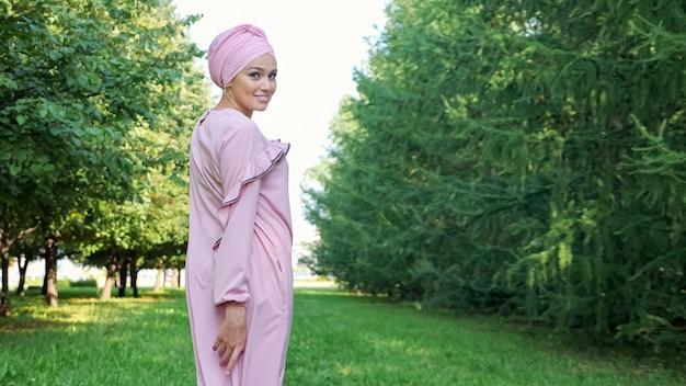 Senhora elegante em um longo vestido roxo e hijab projetado caminha ao longo do caminho do parque verde com um sorriso alegre sob a luz do sol