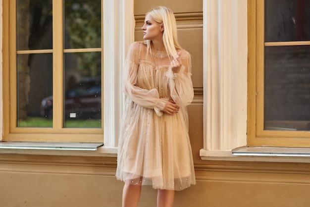 Senhora elegante em um vestido bege e sapatos de salto alto