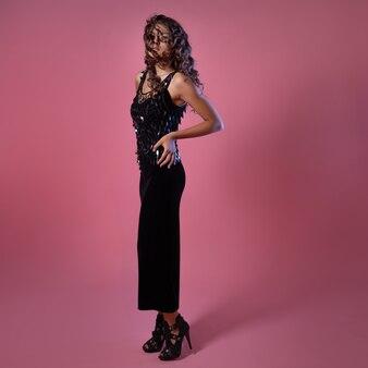 Senhora elegante em um vestido longo de noite preto com lantejoulas, retrato de corpo inteiro de uma bela jovem morena em um fundo rosa