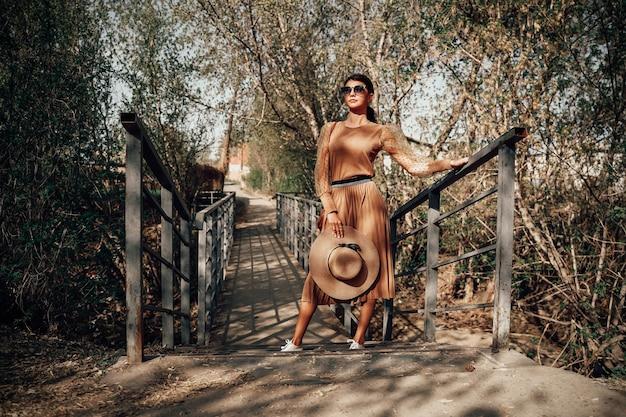 Senhora elegante em uma roupa bege e um chapéu com óculos de sol. detalhes do look do dia a dia. estilo minimalista elegante. estética bege. livro de looks de moda. outono, primavera, conceito de temporadas de verão.