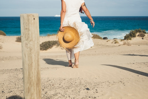 Senhora elegante em vestido branco e chapéu de palha, caminhando descalço para a praia.