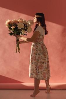 Senhora elegante posando com buquê de flores