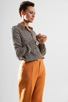 Senhora elegante, vestida com calças clássicas e uma camisa em branco