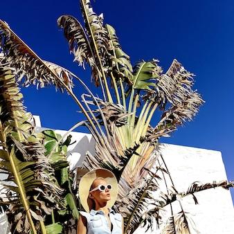 Senhora em acessórios de moda chapéu e óculos de sol na palma da mão apenas vibrações de praia