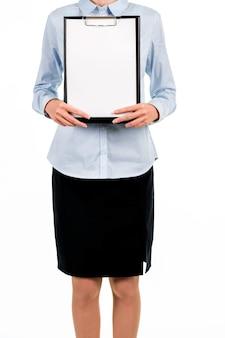 Senhora em pé com a área de transferência em branco. jovem fêmea segurando a área de transferência em branco. por favor, assine o acordo. as informações de contato estão escritas aqui.
