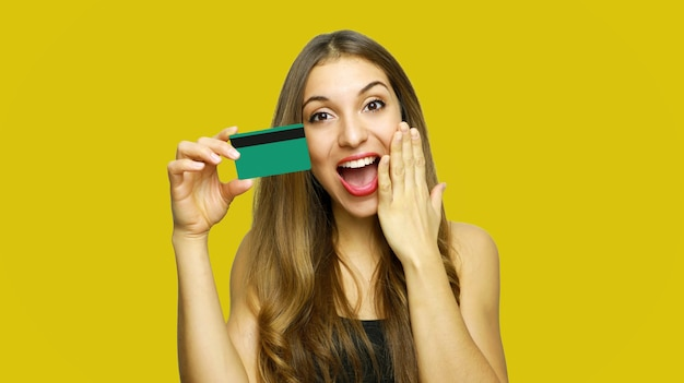 Senhora em pé segurando um cartão de débito na mão