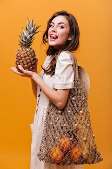 Senhora em roupa de algodão lambe, segura abacaxi e sacola de barbante com laranjas em fundo isolado.