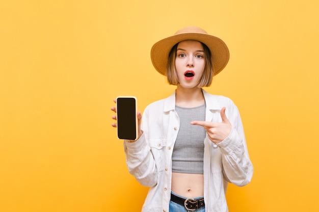 Senhora em roupas de verão e chapéu fica em um amarelo, aponta o dedo para a tela preta de um smartphone na mão