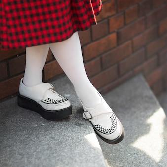 Senhora em sapatos de estilo punk rock, saia de padrão tartan preto e vermelho, meia branca com profundidade de campo, foco no sapato