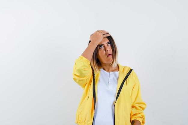 Senhora em t-shirt, casaco mantendo a mão na cabeça e parecendo irritada, vista frontal.
