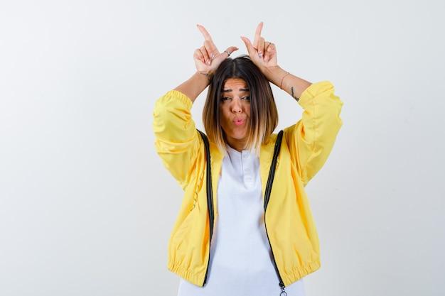 Senhora em t-shirt, jaqueta mantendo os dedos sobre a cabeça como chifres de touro e parecendo engraçada, vista frontal.