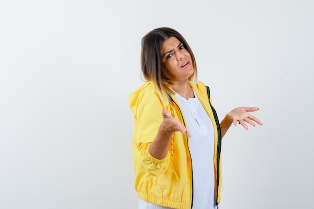 Senhora em t-shirt, jaqueta mostrando um gesto desamparado e parecendo confusa, vista frontal.