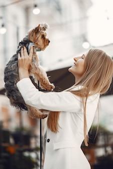 Senhora em um café de verão. mulher sentada à mesa. famale com um cachorro fofo.