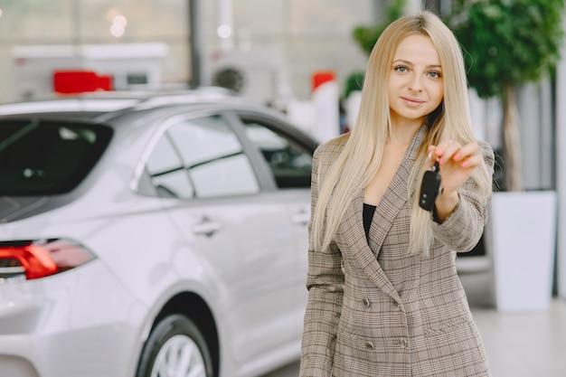 Senhora em um salão de automóveis. mulher comprando o carro. mulher elegante em um terno marrom.