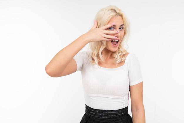Senhora em uma camiseta branca flerta batendo os olhos em um fundo branco com espaço de cópia