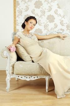 Senhora em vestido de noite no sofá real