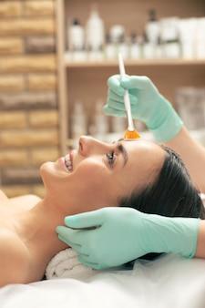 Senhora emocional e gostando do procedimento de peeling de limpar a pele do rosto com uma escova macia