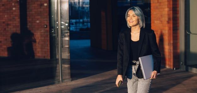 Senhora encantadora andando na rua com um laptop, sorrindo e segurando o telefone